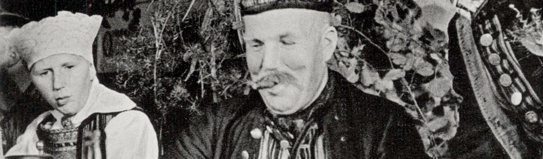 Zdjęcie archiwalne. W centrum głowa uśmiechniętego mężczyzny, po jego prawej stronie przyglądająca mu się kobieta.