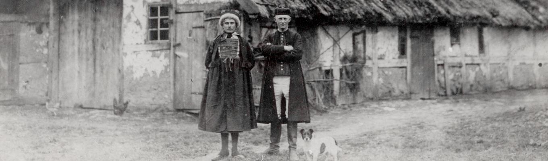 Zdjęcie archiwalne. Para jamneńczyków w tradycyjnych strojach. W tle kurna chata.