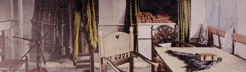 Fragment pocztówki archiwalnej. Wnętrze chaty z krzesłami jamneńskimi i wnękami łóżkowymi.