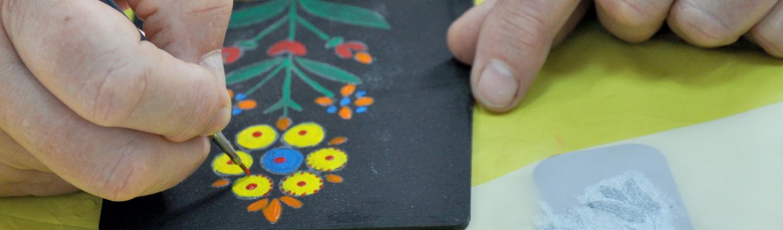 Zbliżenie na dłonie dekorujące deseczkę wzorami jamneńskimi.