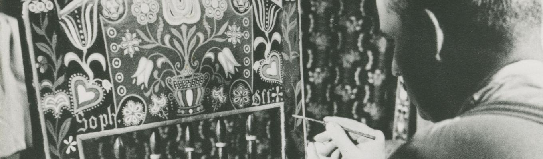 Zdjęcia archiwalne. Męźczyzna maluje zaplecek krzesła we wzory jamneńskie.