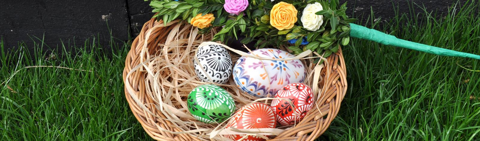 W koszyku leży pięć dekorowanych woskiem pisanek. Na obrzeżach koszyka leży palma wielkanocna.