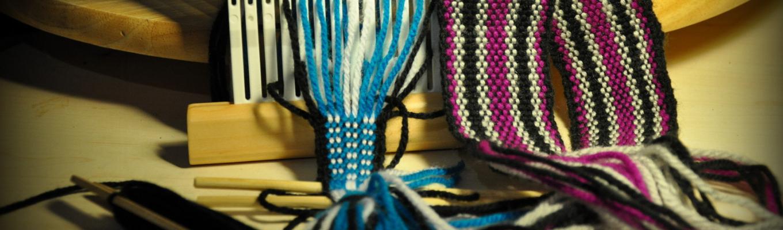 Na środku rozpoczęta krajka w kolorze niebiesko-białym, po prawej stronie fragment gotowej krajki w kolorze fioletowo-czarno-białym