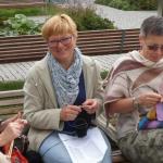 Światowy Dzień Dziergania. Cztery panie siedzą na ławce i robią na drutach