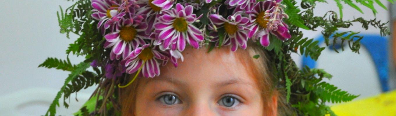Bliski kadr na twarz dziewczynki. Widoczne tylko oczy. Na głowie wianek ze świeżych kwiatów.