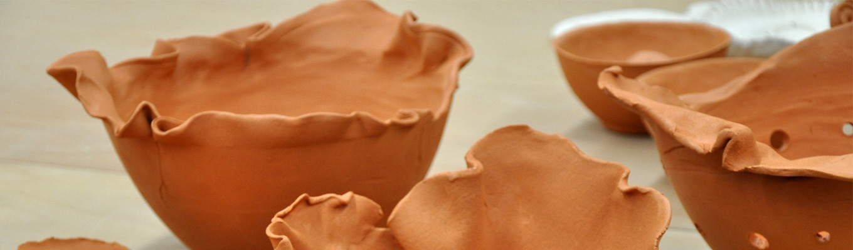 Fragmenty kilku glinianych misek o różnych kształtach.