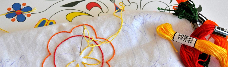 Na pierwszym planie białe płótno z rozpoczętym haftowaniem - kwiatek w kolorach żółtym, pomarańczowym i czerwonym. W płótno wbita igla. Po prawej stronie mulina w kolorze żółtym, czerwonym i zielonym. W tle kartka ze wzorem jamneńskim.