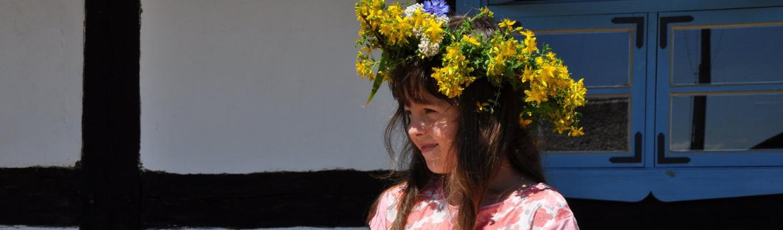 Po lewej stronie popiersie dziewczynki w wianku z żółtych kwiatów polnych. W tle ściana chałupy z oknem.