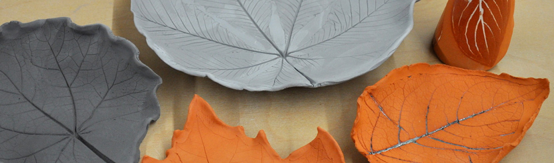 Fragment talerzyka w kształcie liścia wykonany z szarej gliny