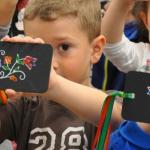 Grupa dzieci trzymających czarne deseczki z wymalowanymi, kolorowymi wzorami jamneńskimi.