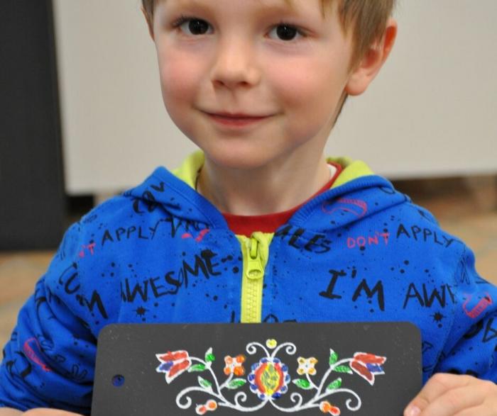 Uśmiechnięty chłopiec trzyma deseczkę z namalowanym wzorem jamneńskim.