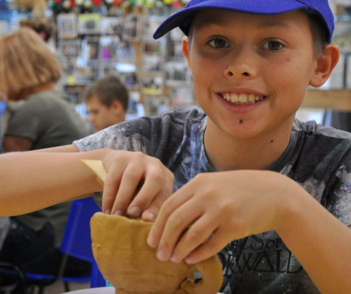 Zbliżenie na uśmiechniętego chłopca lepiącego w glinie.