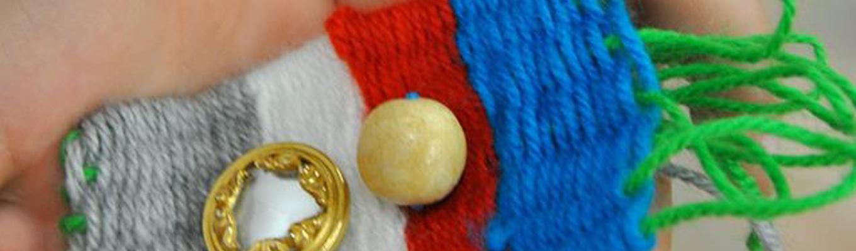 Fragment kolorowej tkaniny z naszytą drewnianą kulką i metalową ozdobą.