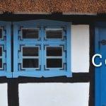 Zbliżenie na front chałupy kmiecej. Po lewej steonie okna z niebieskimi okiennicami, po prawej drewniane drzwi pomalowane na niebiesko.