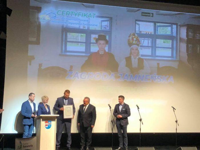 Na scenie stoi 5 osób. Po środku p.o. dyrektor Muzeum w Koszlainie Krzysztof Jedynak odbiera certfikat dla Najlepszego Produktu Turystycznego Pomorza Zachodniego.