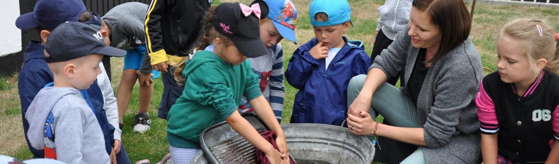 Lekcja muzealna. Grupa dzieci z jedną dorosłą osobą siedzi naokoło dużej, metalowej balii. Jedna z dziewczynek trze czerwony materiał o tarę.