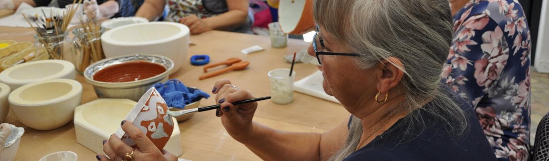Na pierwszym planie postać kobiety w profilu. Trzyma ona miseczkę, którą maluje. W tle stół zasrawiony formami ceramicznymi i narzędziami do pracy w glinie.