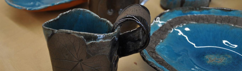 kubek wykonany z gliny, wypalony i pokryty czarnym szkliwem