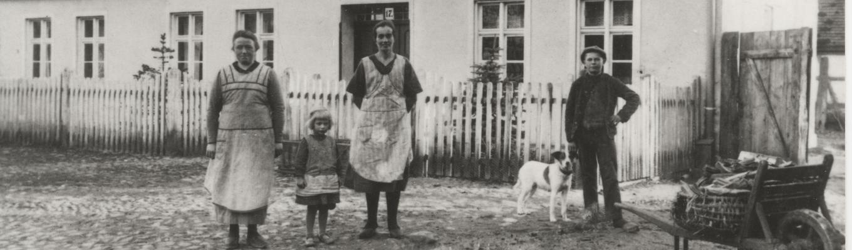 Na pierwszym planie stoją dwie kobiety, pomiędzy nimi dziewczynka, po prawej stronie stoi chłopiec z pieskiem przy nodze. W tle płotek i chalupa.